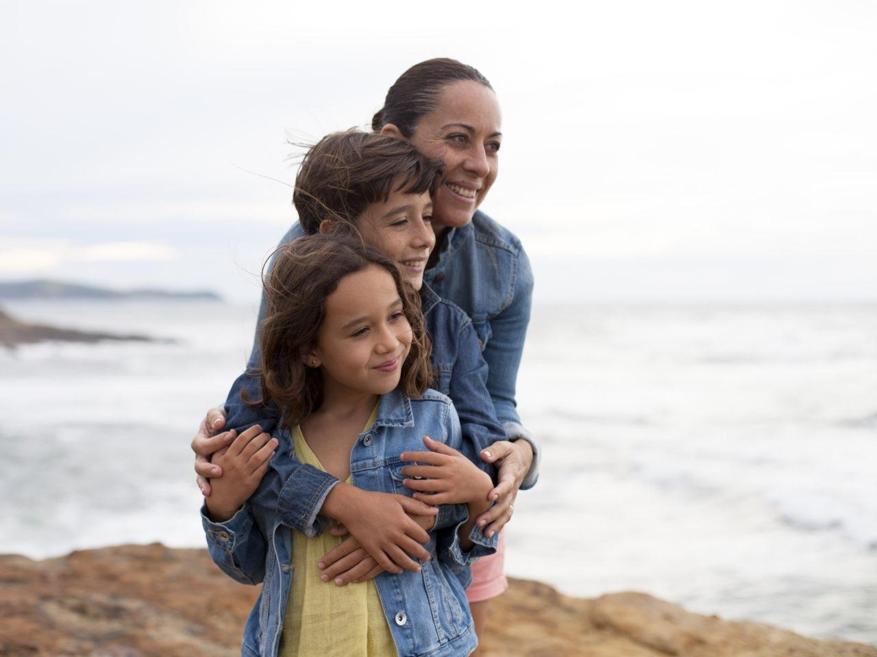 Madre abrazando a sus hijos junto al  mar